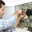 Electrician fixing cable in domestic electrical box — Stock Photo