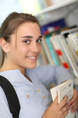 Girl reading book from school library — Stock Photo