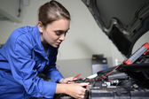 Student girl in mechanics working on car engine — Stock Photo