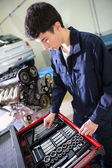 Student in mechanics working on car engine — Stockfoto