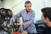 Trainer teaching student how to fix car engine — Stock Photo