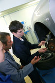 Instructor showing students how to repair car wheel — Stock Photo