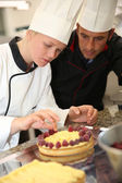 Pastry cook teaching student to make a cake — Stock Photo