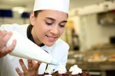 Pastry cook putting whipped cream on cake — Stock Photo