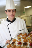 Young pastry cook holding tray of pastries — Stock Photo