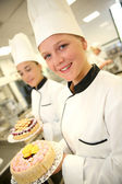Students girls in pastry holding cakes — Stock Photo