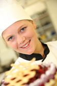 Young confectioner holding cake — Stock Photo