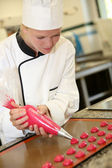 Pastry cook student making red cookies — Stock Photo