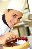 Girl at training school making cake — Stock Photo