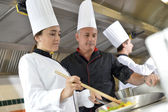 Chef teaching student how to prepare wok dish — Stock Photo