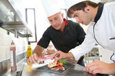 Student in catering to prepare foie gras dish — Stock Photo