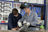 Trainee with instructor using welding machine — Stock Photo