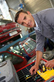 Coachbuilder standing in autoshop — Stock Photo