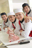 Young butchers in school kitchen — Stock Photo