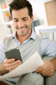 Man reading news on both paper and internet — Stock Photo