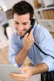 Homem no escritório atender o telefone — Fotografia Stock