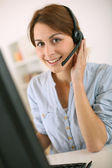 Woman at work talking on phone with headset — Stock Photo