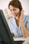 Mujer en el trabajo hablando por teléfono con auricular — Foto de Stock