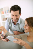 Couple using smartphone at home — Stock Photo
