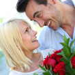 Stock Photo: Man giving red roses to woman