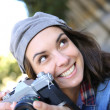 Trendy girl holding camera — Stock Photo