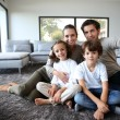 Stock Photo: Family sitting on carpet
