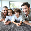 Family relaxing on carpet — Stockfoto