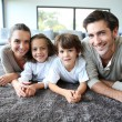 Stock Photo: Family relaxing on carpet