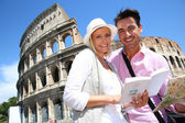 Couple reading guide book by the Coliseum — Stock Photo