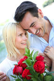 Man giving red roses to woman — Stock Photo
