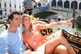 Couple on a Gondola ride passing by Rialto bridge — Stock Photo