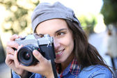 Trendy girl holding camera — 图库照片