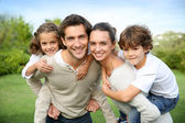 Parents giving piggyback ride to children — Stock Photo