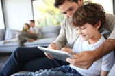 Father and son playing with digital tablet — Stock Photo