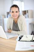 Woman working in office on laptop — Stockfoto