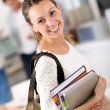 Girl holding books and going to class — Stockfoto