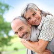 Senior man giving piggyback ride to woman — Stock Photo #35319147