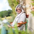 Senior woman using tablet in garden — Stock Photo