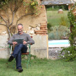 Man relaxing with tablet in private garden — Stock Photo #35319285