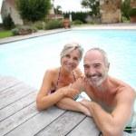 Active senior couple in resort pool — Stock Photo