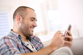 Man at home using smartphone — Stock Photo