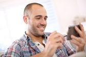 Homme à la maison à l'aide de smartphone — Photo