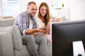 Couple at home looking for tv progam — Stock Photo