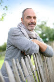 Mature man standing by fence — Stock Photo