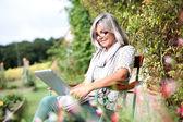Senior woman using tablet in garden — Stock Photo