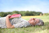 Woman reading book on the grass — Stock Photo