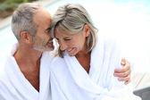 Couple in bathrobe by resort pool — Stock Photo
