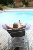Senior man reaxing in long chair — Zdjęcie stockowe