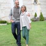 Mature couple walking in garden — Stock Photo #35320533
