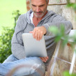 Mature man using tablet on a bench — Foto de Stock